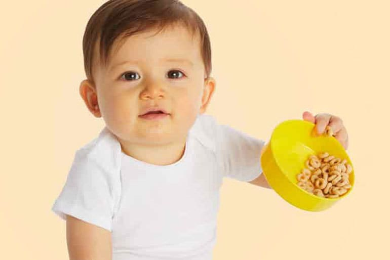 Baby with a bowl of Cheerios that are about to spill.
